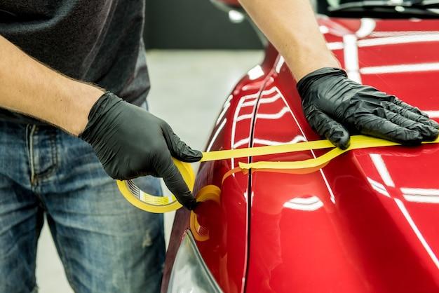 Работник автосервиса наклеивает на детали автомобиля защитную ленту перед полировкой. Premium Фотографии
