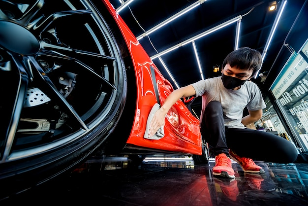 Car service worker polishing car with microfiber cloth. Premium Photo