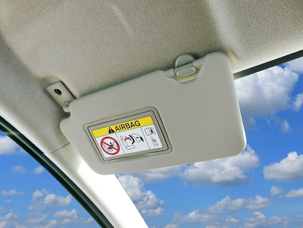 Car sun visor and warning signs of airbag system in car. Premium Photo