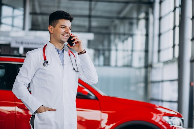 Car technician with stethoscope in a car showroom talking on the phone Free Photo