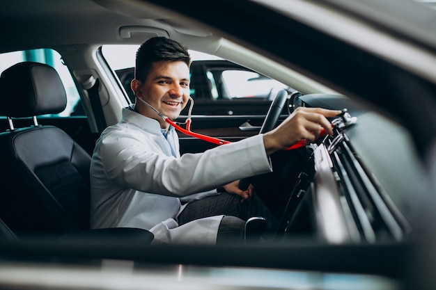 Car technician with stethoscope in a car showroom Free Photo