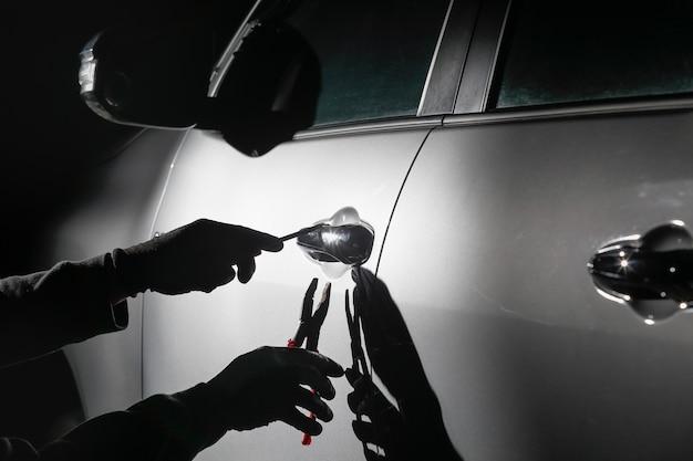 Car thief using a tool to break into a car Premium Photo