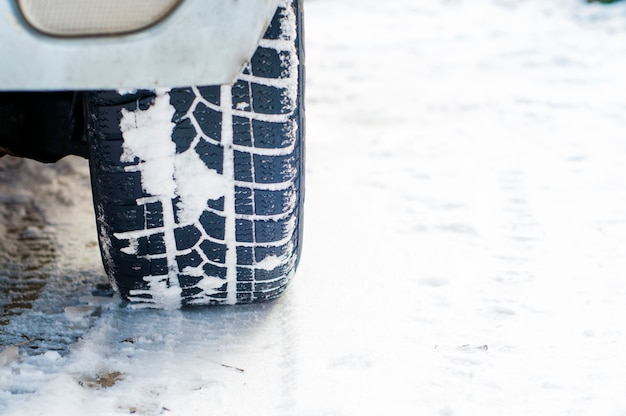 Car tires on winter road covered with snow. vehicle on snowy alley in the morning at snowfall Free Photo