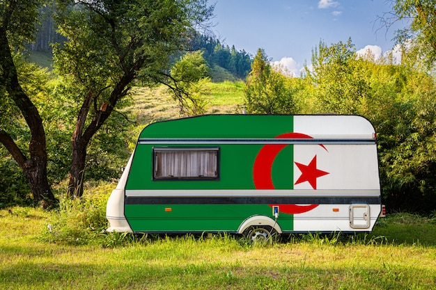 A car trailer, a motor home, painted in the national flag of algeria stands parked in a mountainous. Premium Photo