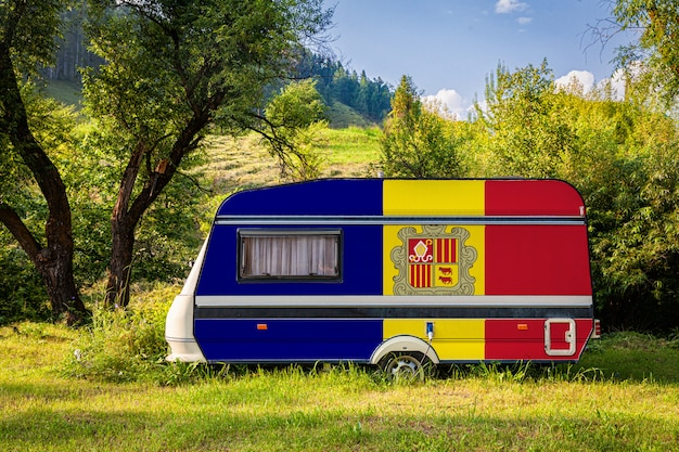 A car trailer, a motor home, painted in the national flag of andorra stands parked in a mountainous. Premium Photo
