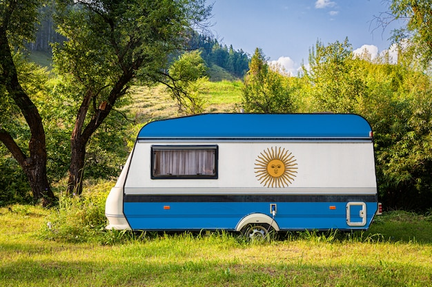 A car trailer, a motor home, painted in the national flag of argentina stands parked in a mountainous. Premium Photo