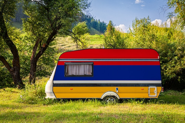 A car trailer, a motor home, painted in the national flag of armenia stands parked in a mountainous. Premium Photo
