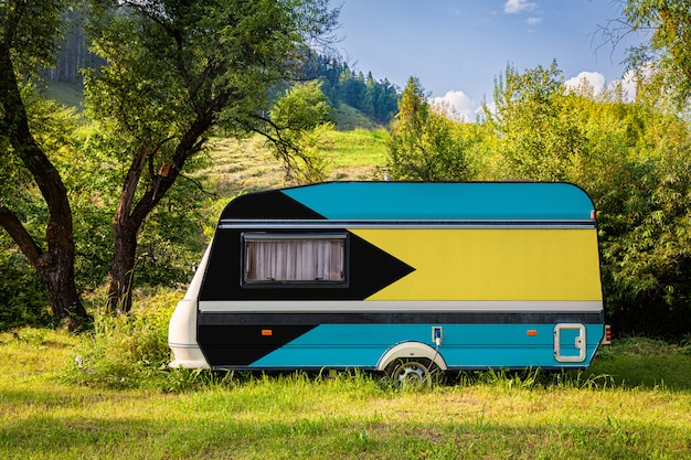 A car trailer, a motor home, painted in the national flag of bahamas stands parked in a mountainous. Premium Photo