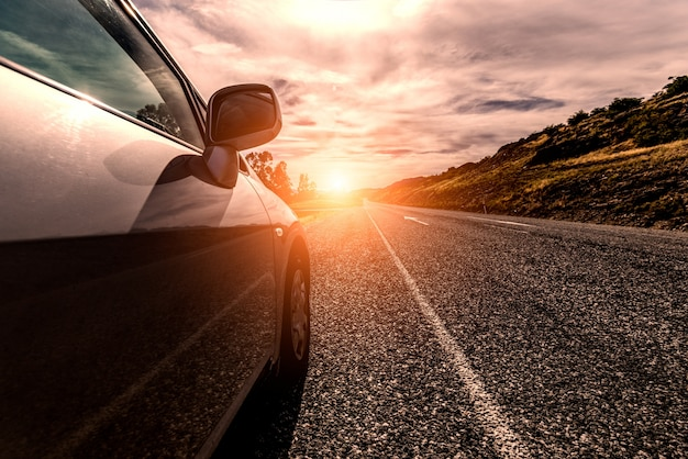 Car travelling by a sunny road Free Photo