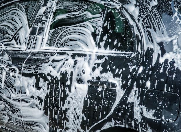 Car wash bubbles with soap. close up of car washing process. Premium Photo