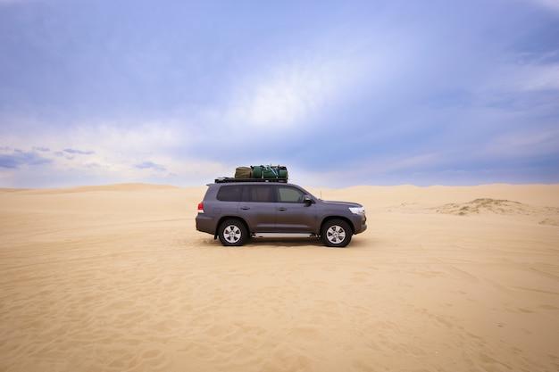 Auto con bagagli sopra nel deserto sotto un cielo nuvoloso durante il giorno Foto Gratuite