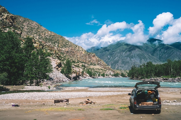 Car with open large trunk near mountain river with turquoise water. Premium Photo