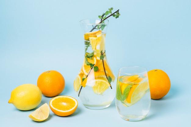 Carafe with oranges on blue background Free Photo