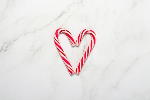 大理石の背景にハートの形に折りたたまれたキャラメルの杖。コンセプトクリスマス、新年、休日のお菓子。フラットレイ、上面図。 Premium写真