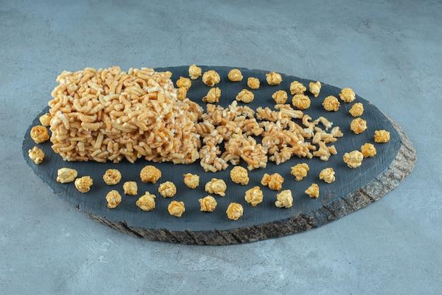 Torta ricoperta di caramello e un mazzo di popcorn al caramello su una tavola su una superficie di marmo Foto Gratuite