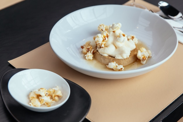 Caramel custard with cream that topping with popcorn. served in white plate. Premium Photo