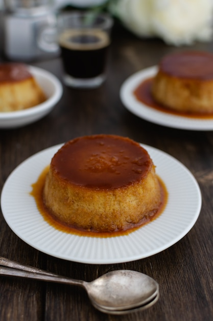 Caramel flan, crema catalana dessert on dark brown woden table Premium Photo