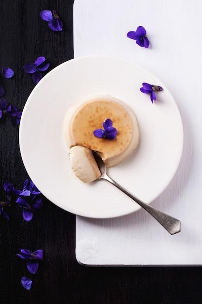 Caramel pannacotta with violet flowers Premium Photo