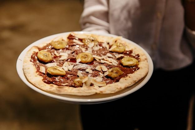 Caramelized banana nutella pizza. ingredients are pizza dough Premium Photo