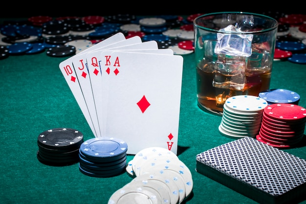Card; casino chips and glass of whiskey on poker table Free Photo