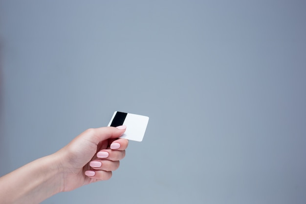 The card in a female hand is on gray wall Free Photo