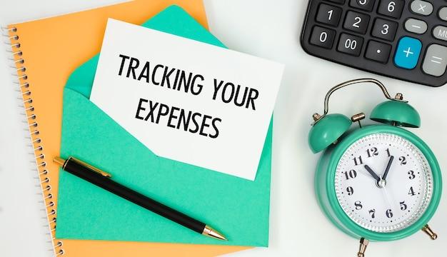 비용, 시계, 계산기, 펜 추적 텍스트가있는 우편 봉투에 카드. 프리미엄 사진