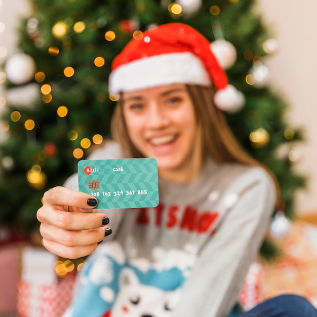 Card shown by woman in christmas hat Free Photo