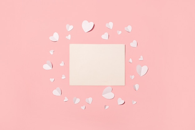 Card and white paper hearts on a pink background. composition valentine's day. banner. flat lay, top view. Premium Photo