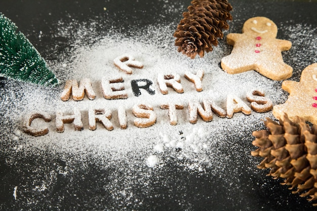 Card with gingerbread cookies. baked letters merry christmas, fir tree. christmas card Premium Photo