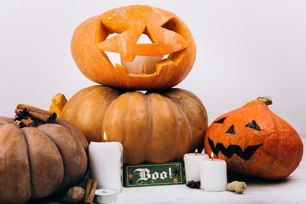 Карточка с надписью «бу» стоит перед суровыми тыквами хэллоуина Бесплатные Фотографии