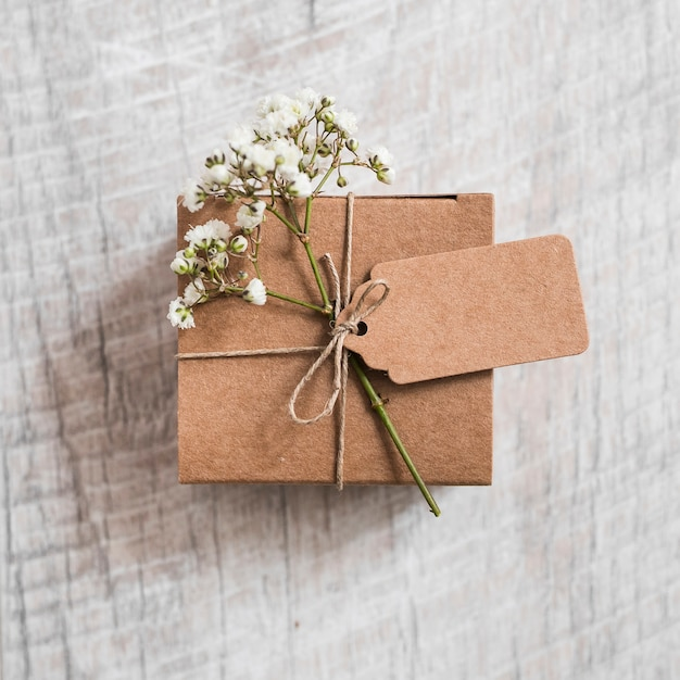 Cardboard box and baby's-breath flower tied with string on wooden backdrop Free Photo