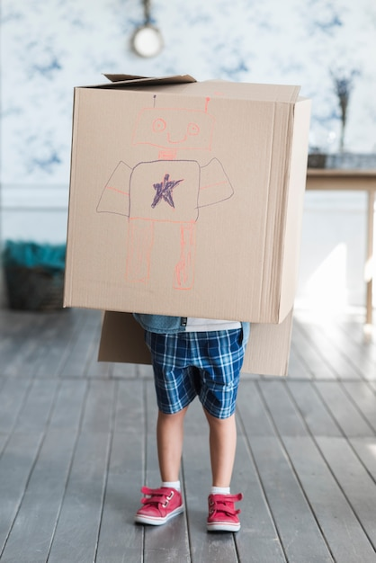 Cardboard box drawn with robot over the boy standing in the room Free Photo