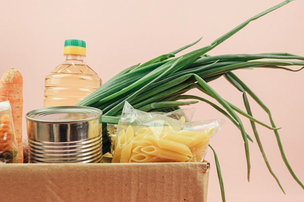 Cardboard box isolated on a pink background with butter, canned goods, onions, cookies, pasta, fruits. food delivery. Premium Photo