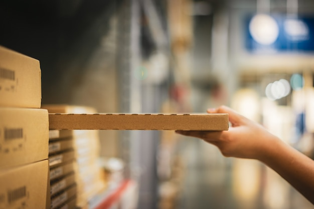 Cardboard box package with blur hand of shopper woman picking product from shelf in warehouse. Premium Photo