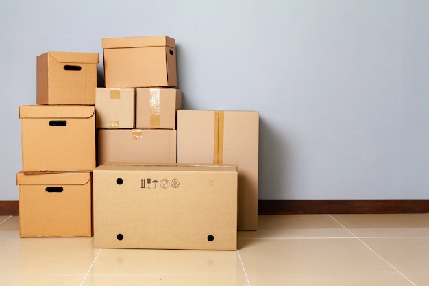 Cardboard boxes for moving on the floor against grey wall Premium Photo