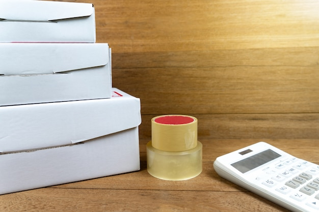 Cardboard boxes stacked with calculator on wooden table. Premium Photo