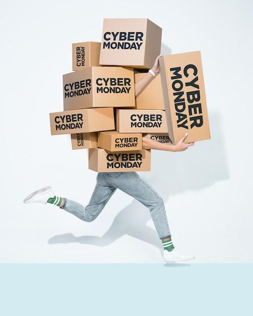 Scatole di cartone con iscrizione cyber monday nelle mani di un giovane Foto Gratuite