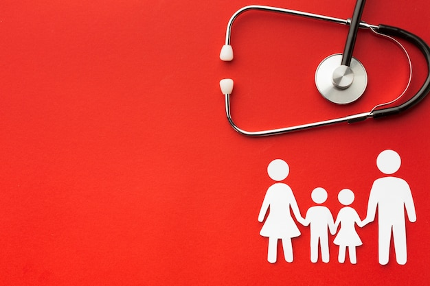 Cardboard family shapes with stethoscope and copy space Premium Photo