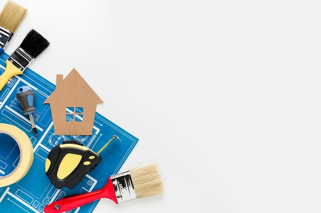 Cardboard house arrangement and repair tools with copy space Premium Photo