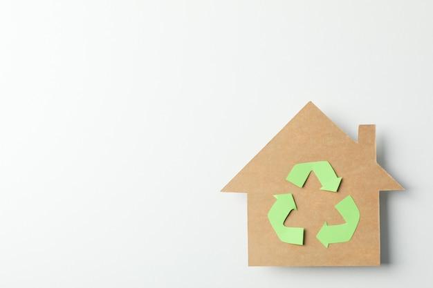 白い背景の上の記号をリサイクルで段ボールの家、テキスト用のスペース Premium写真