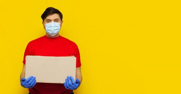 黄色の壁にcardboxを保持している医療マスクの配達人 Premium写真