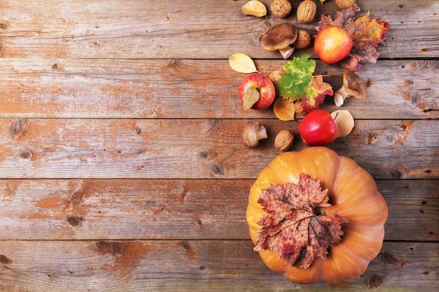 Оранжевая тыква с грибами cardoncelli, яблоками, грецкими орехами и красочными листьями на старых простоватых деревянных досках. осенний день благодарения фон Premium Фотографии