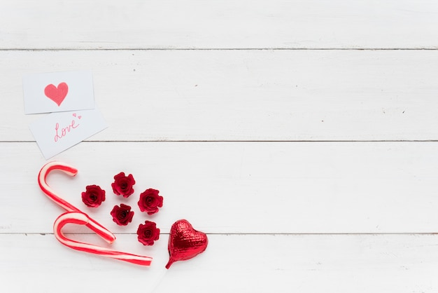 Cards with love inscription near decorative heart and candy canes Free Photo