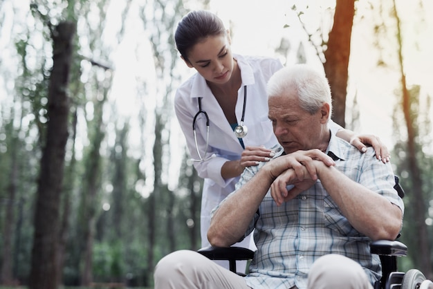 Care doctor comforts the sad old man Premium Photo
