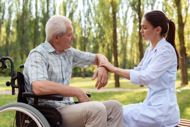 Care doctor probes the old man's elbow Premium Photo