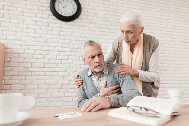 Care old woman is worried because of pain in husband's heart Premium Photo