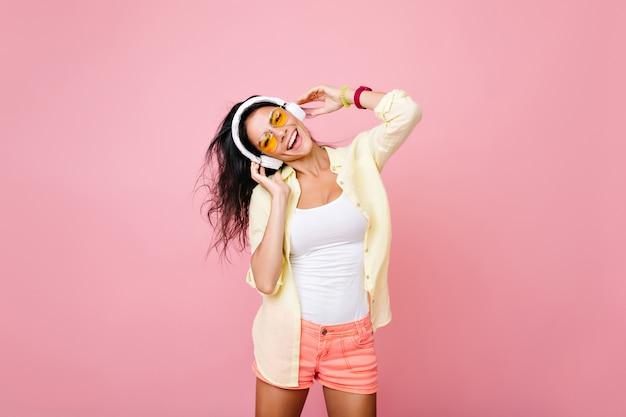 幸せな表情で好きな歌を歌う夏服を着たのんきなアジアの女性。ダンス中に楽しんでいる黄色いジャケットの魅力的なヒスパニック系の女の子の屋内の肖像画。 無料写真