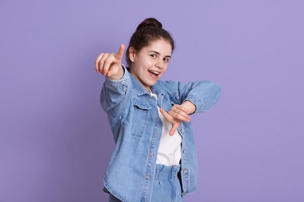 屈託のない魅力的な女性を探して指して立っているライラックの壁の上に孤立、スタイリッシュなデニムジャケットと白いシャツ、結び目とブルネットの女性。 Premium写真