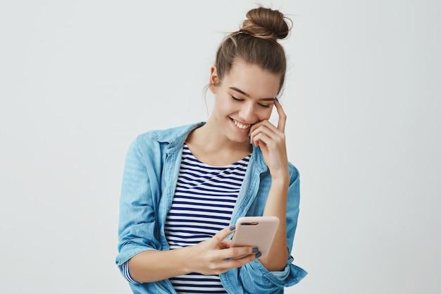 Giovane donna europea attraente spensierata che sorride felicemente tenendo smartphone che guarda esposizione Foto Gratuite