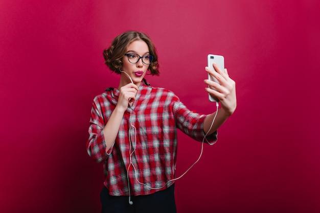 Беззаботная шатенка в клетчатой повседневной рубашке делает селфи. фото веселой молодой леди в очках, позирующей с выражением лица целуя и использующей телефон. Бесплатные Фотографии